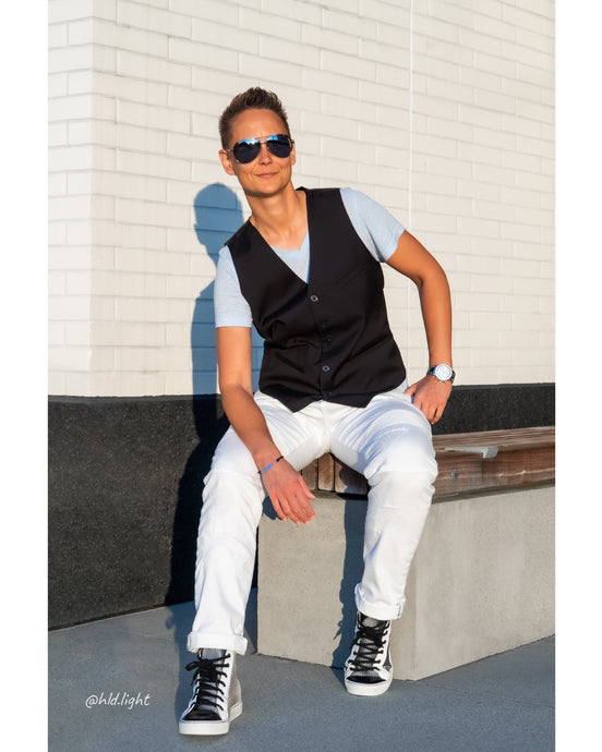 Tomboy-Model-Tomboy-Outfit-Date-Idea-Blue-V-Neck-T-shirt-Black-Vest-White-Ripped-Jeans-Aviator-Sunglasses-Silver-Watch-Silver-Bracelet-Short-Hair-Black-and-White-Vegan-Sneakers-Gender-Neutral-Nonbinary-Androgynous-Summer-Fashion