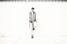 Load image into Gallery viewer, Tomboy-Model-Tomboy-Style-Black-Snapback-White-Hoodie-Printed-Sleeve-Grey-Metallic-Puffy-Vest-Black-and-White-Zara-Joggers-Black-Sneakers-Gender-Neutral-Androgynous-Fashion