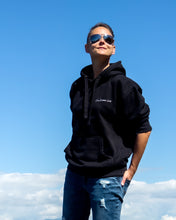 Load image into Gallery viewer, Tomboy-Outfit-Tomboy-Style-Black-Hoodie-Ripped-Blue-Jeans-Blue-Salomon-Runners-Aviator-Sunglasses-Ocean-Tomboy-Hair-Gender-Neutral-Nonbinary-Androgynous-Summer-Fashion