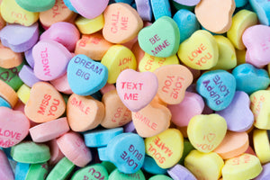 A large colourful pile of sweethearts candy with conversational Valentine's Day messages conveying love and adoration.