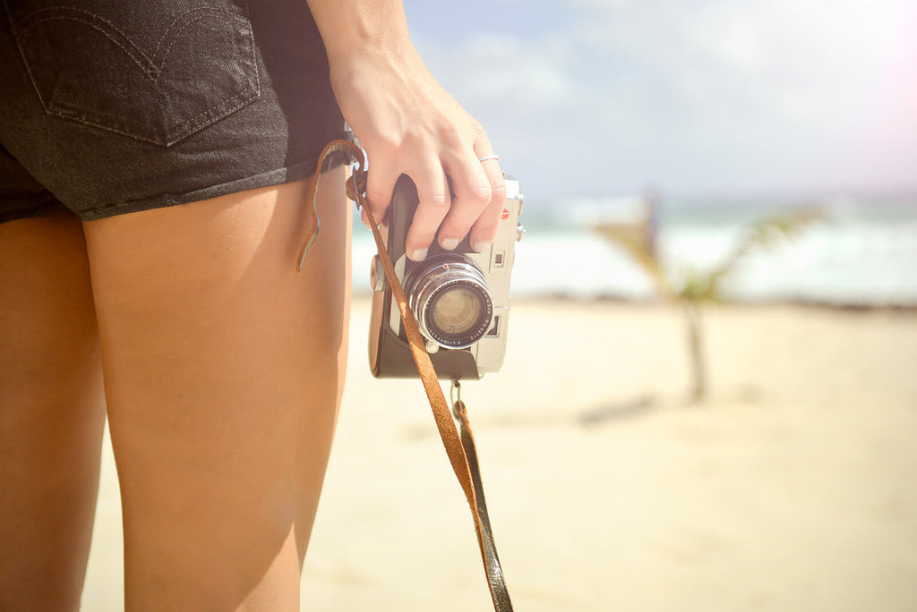 Woman with camera on beach