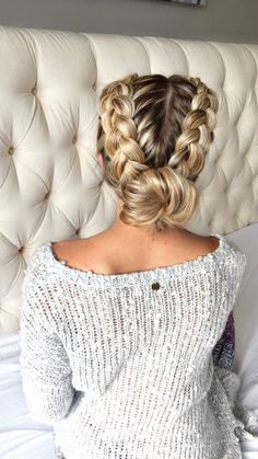 Girl with two french braids leading down to a ballerina bun. She is facing away so that you can see the whole hairstyle.