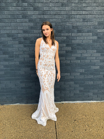 Olivia is wearing a white sheath prom gown, she is standing in front of a blue brick wall and her hair is down and straight.