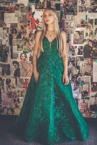 girl inside of a prom boutique taking pictures in a green prom dress
