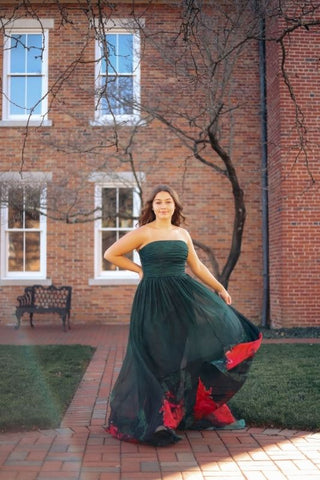 green ball gown prom dress with a building backdrop