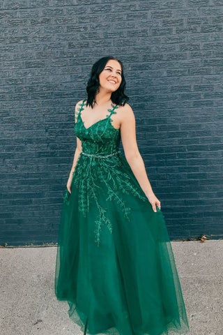 girl looking back in her green prom dress with thin straps and a-line bottom
