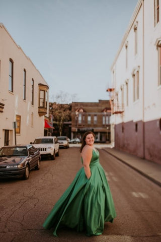 girl in the city wearing a green ballgown prom dress