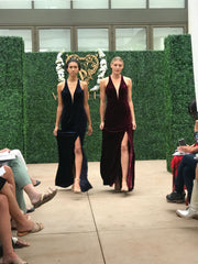 Two models walking the runway wearing dresses with a low plunge neckline and a high slit
