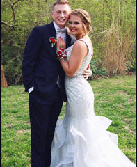 XO Babe, Liv, is posing with her prom date. She is in a silver mermaid gown and he is wearing a black tux. She has on a bright red corsage and he is wearing a red tie.
