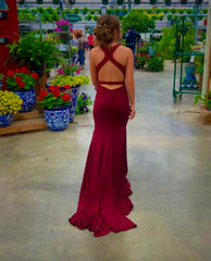 Girl walking away in her red prom dress. The back of her dress has a lot of straps, so her hair is in an updo.