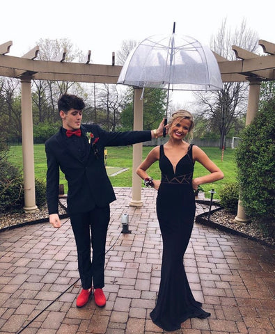 XO Babe, Chaste,  is standing under a clear umbrella, held by her date. She is in a black sheath gown with triangle cut outs at the wast. Her date is wearing an all black tux with bright red shoes and tie.