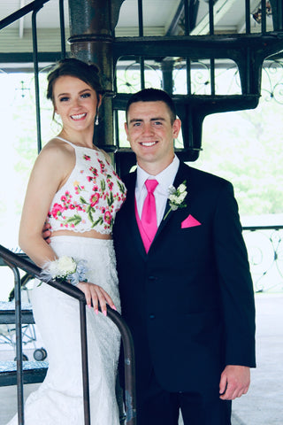 Olivia is standing next to her date. Scott, on a black spiral staircase She has on a white two piece gown. The top has pink, yellow, and green flowers embroidered on it. Scott is wearing a black tux, with a hot pink tie.