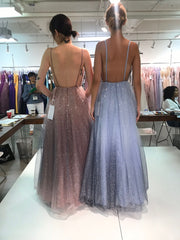two models standing with their backs to us to show us the low back detail on their gowns.