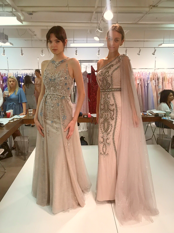 two models on a runway. One is wearing a blush sheath gown with lots of beading. The other is wearing a one shoulder blush gown with beading down the front and a cape coming off the one shoulder.