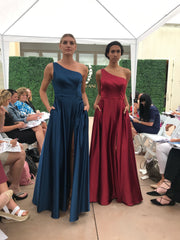Two models walking down the runway. One is wearing a one shoulder, navy blue prom dress. The other is wearing a one shoulder, wine colored prom dress.