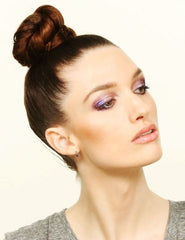 Girl with a sleek top knot bun. Her head is tilted up and she is wearing purple eye shadow.