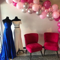Inside XO's storefront. There are two hot pink velvet chairs next to two prom gowns. One is a Royal Blue A line Gown and the other is a white off the shoulder two piece sheath gown. There is a Hot Pink, Silver, and Light Pink balloon arch on the right going over the top of the chairs and dresses.