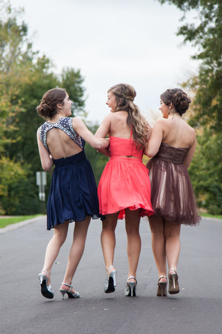 Three girls walking away in their homecoming dresses. All of their hair is done according to the back of their gown.