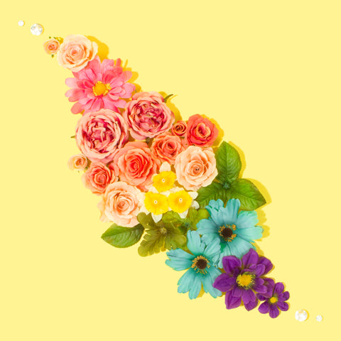 A rainbow of flowers are arranged in a diagonal diamond shape. They are on a light yellow backdrop.