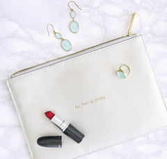 A white clutch that is laying on a marble background. It has a tube of red lipstick and teal earrings laying on top of it.