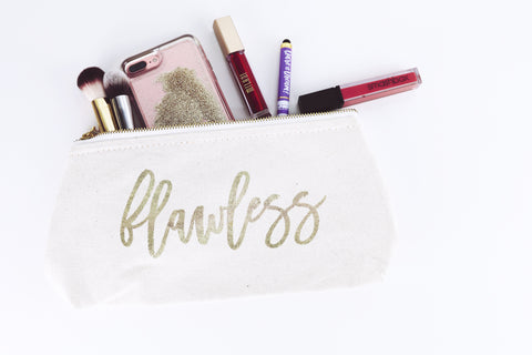 A white clutch with gold writing that says Flawless on it is laying on a white background. It has makeup brushes, lipstick, an iphone, and a pen sticking out of the top.