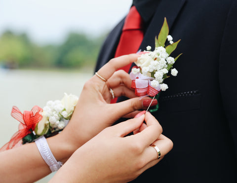 Female hands are placing a boutonniere with white flowers and red ribbon on her date's tux.