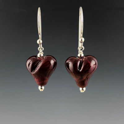 Handmade red puffy heart glass beads dangle from sterling silver Bali ear wires with sterling silver beads at the top and bottom of the hearts.