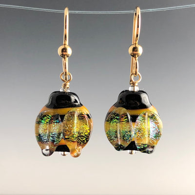 Bee Happy Earrings are handmade glass lentil-shaped yellow and black stripped beads with shimmering wings. They are on gold-filled ear wires with simple small gold-filled balls.