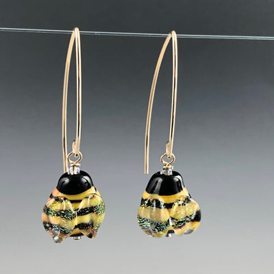 Bee Happy Earrings are handmade glass lentil-shaped yellow and black stripped beads with shimmering wings. They are on long modern shaped gold-filled ear wires.
