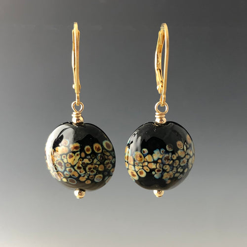 Black lentil-shaped glass beads with speckles of browns and tan. Earrings are gold-filled leverbacks with gold-filled small round beads on top and bottom of the lentil shaped black glass beads.