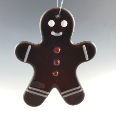 Dark brown glass fused gingerbreadman ornament with white eyes, mouth, cuffs, boots and 3 red glass buttons. Ready to decorate your tree!
