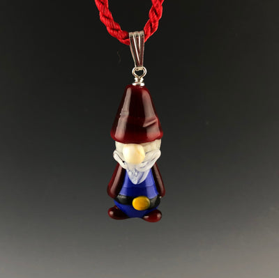 A handmade gnome glass bead pendant with red pointed had, white beard and mustache, round nose, blue outfit with black belt, yellow belt buckle, and red boots. The handmade glass pendant is on a sterling silver bail on a twisted satin cord necklace. Ready for a Scandinavian Christmas!