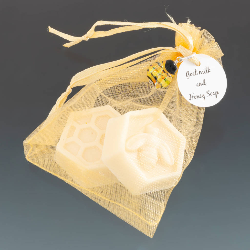 Two guest size goats milk and honey soap hexagonal in shape with bee and honeycomb embosed.  Soaps in gold gorganza bag with a handcrafted glass bee charm and circular tag attached at top with ribbon. All by Becky Congdon