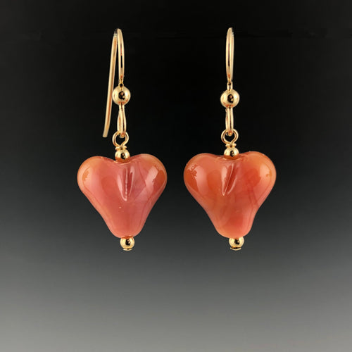 Handmade pink carnelian glass puffy hearts dangle from gold-filled ball ear wires with gold-filled beads at the top and bottom of the hearts.