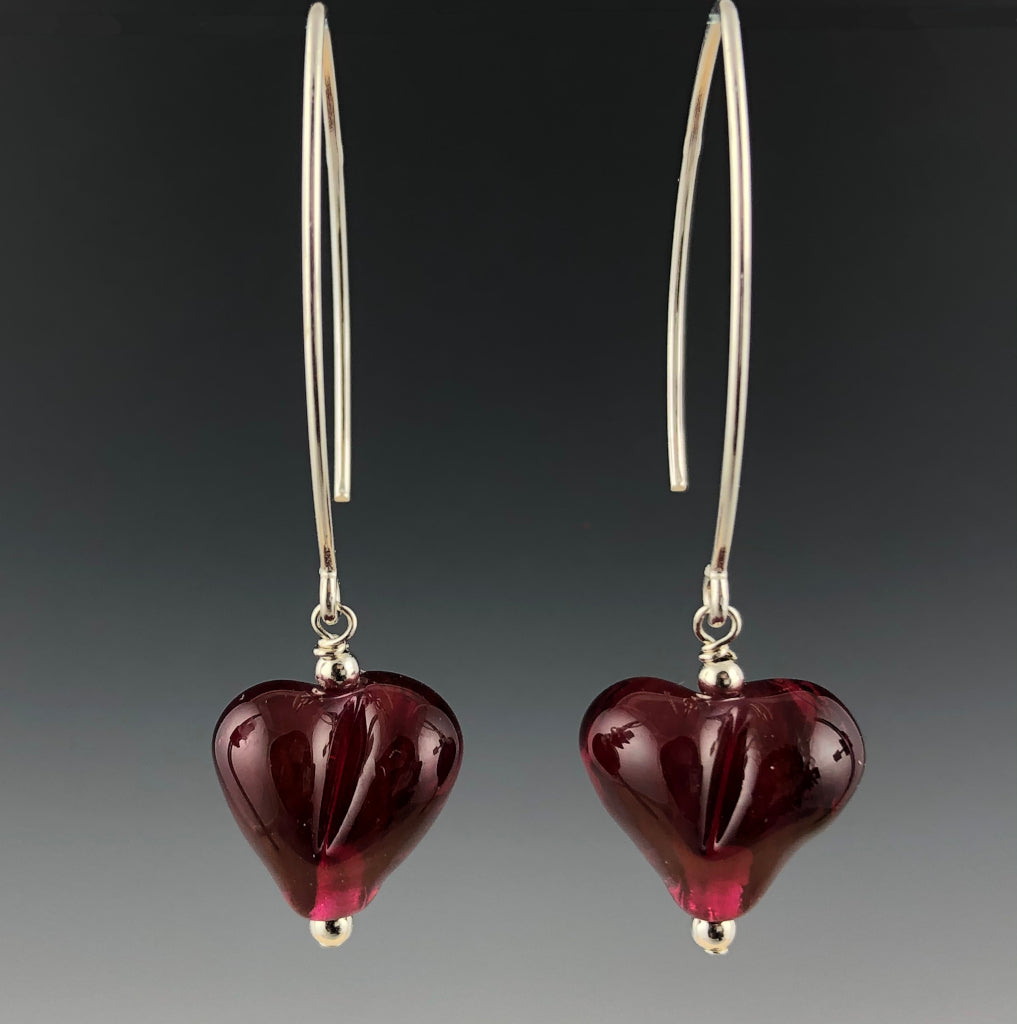Handmade dark ruby pink puffy glass heart beadss dangle from long modern sterling silver ear wires with small sterling silver beads at the top and bottom of the hearts.