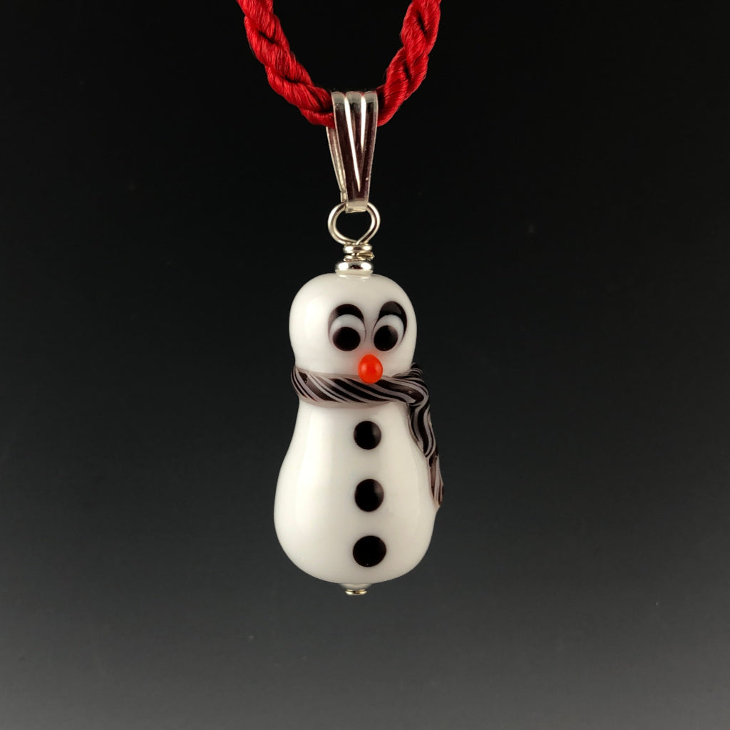 Glass snowman with surprized look with carrot colored nose, 3 black buttons, and white and red twisted scarf around neck and trails down his side. The snowman is on a sterling silver bail on a twisted red satin cord necklace.