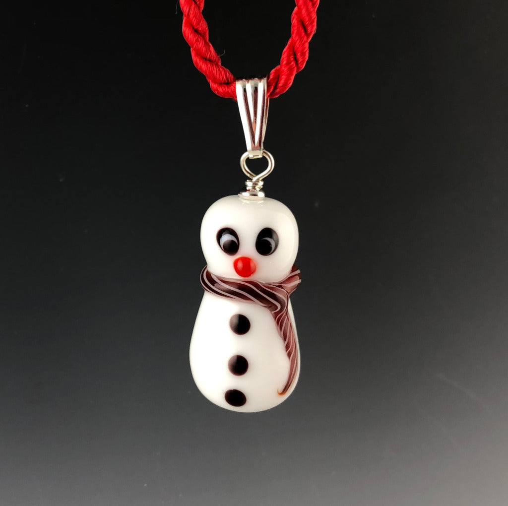 Holiday glass snowman pendant with a cross-eyed looking at his carrot colored nose, 3 black buttons, and white and red twisted scarf around neck and trails down his side. The snowman is on a sterling silver triangular bail on a twisted red satin cord necklace. Ready for Xmas!