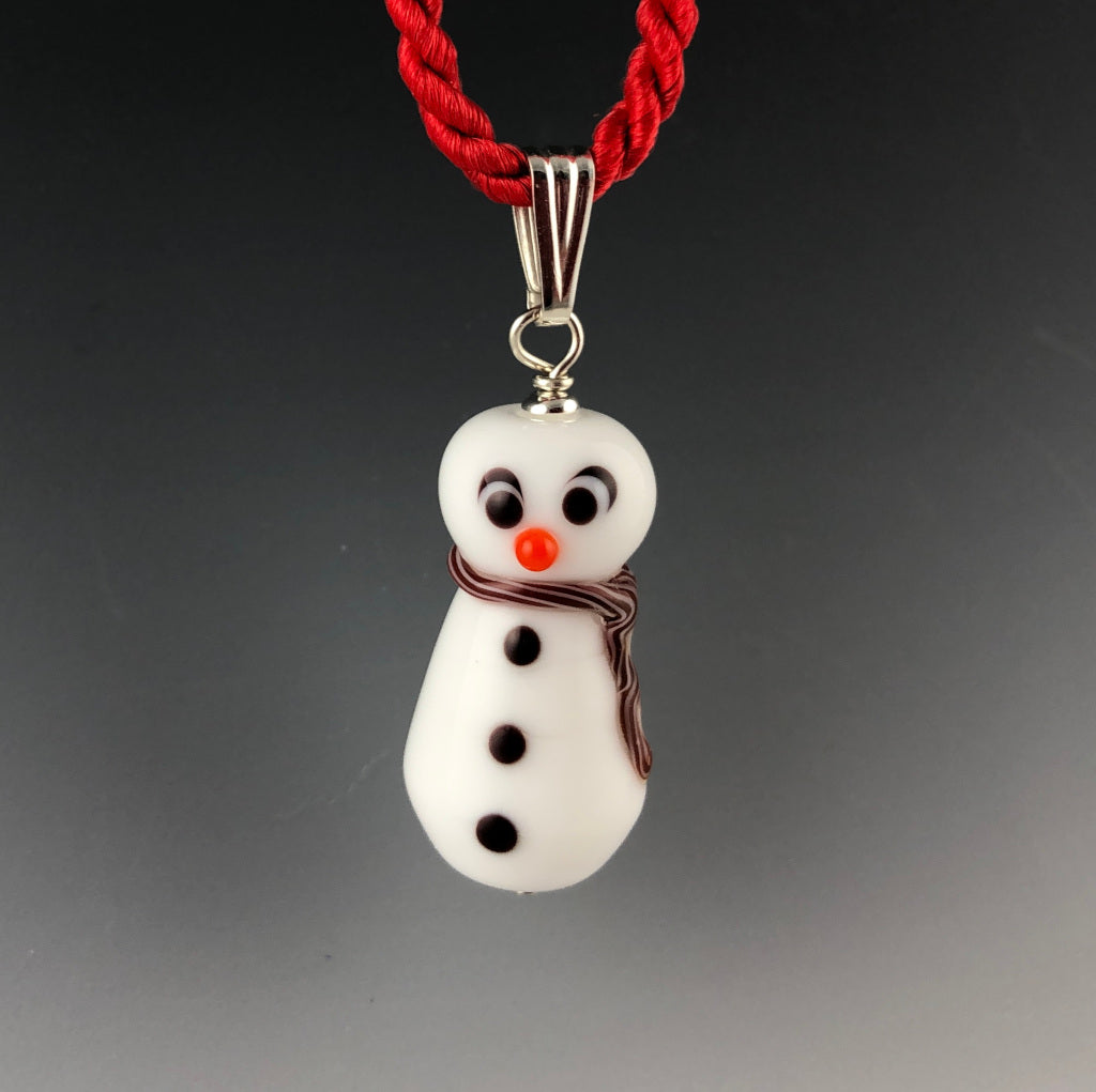 Holiday glass snowman pendant with a cross-eyed looking at his carrot colored nose, 3 black buttons, and white and red twisted scarf around neck and trails down his side. The snowman is on a sterling silver triangular bail on a twisted red satin cord necklace. Ready for Christmas!