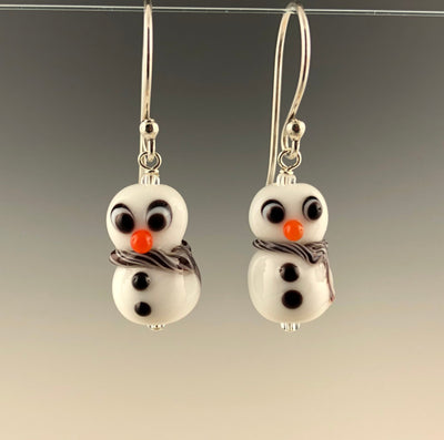 Petite snowmen earrings made of white glass with black and white eyes that look surprized. Each has 2 black buttons down their fronts and orange noses. They have blue and white glass scarves wrapped around their necks. They are on sterling silver ear wires. Ready for the winter holidays!