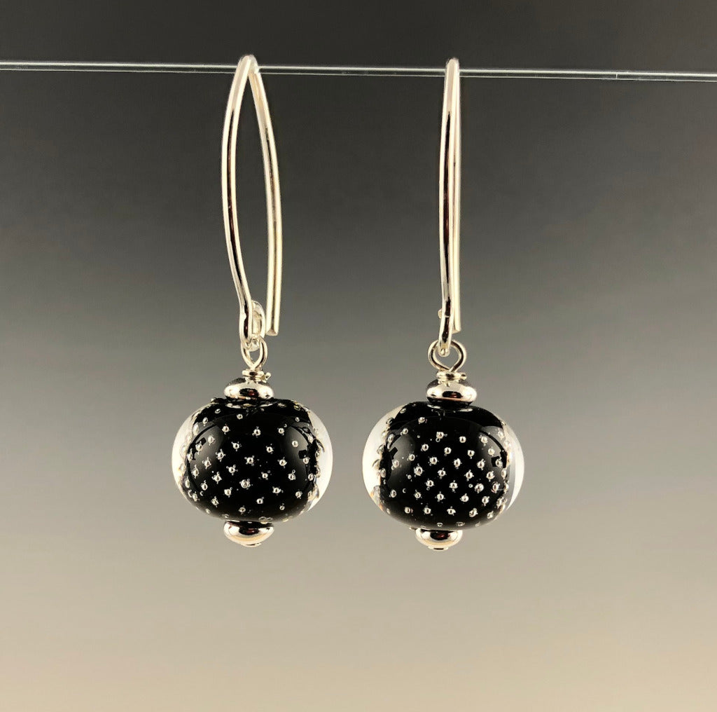 "Handmade flameworked glass beads have sterling silver bubbles on black glass surrounded by clear glass. The beads are assembled with sterling silver beads and sterling silver short contemporary ear wires. The earrings dangle about 1.25""."