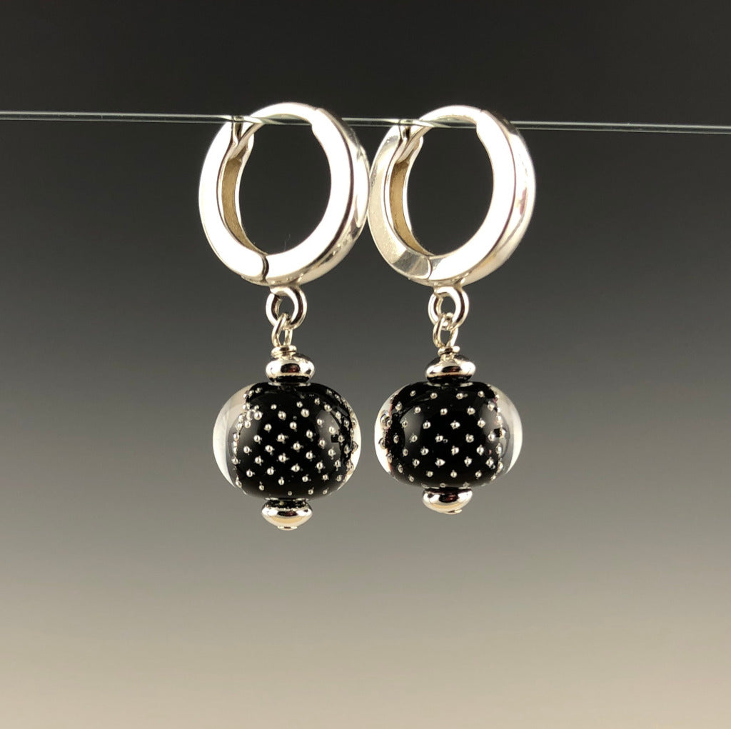Handmade flameworked glass beads have sterling silver bubbles on black surrounded by clear glass. The small round beads are assembled with sterling silver beads and sterling silver small contemporary ear hoops.  (Side View)