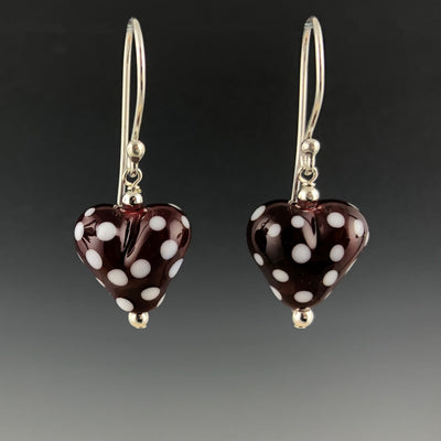 Handmade red with white polka dot puffy glass heart beads dangle from sterling silver Bali ear wires with sterling silver beads at the top and bottom of the hearts.