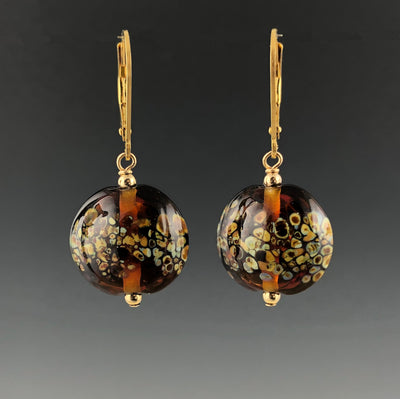 Earrings dangle from gold-filled leverbacks. Each earring has a transparent dark amber lentil-shaped bead with random specks of lighter shades of browns. Each handmade glass bead has a small gold-filled bead on top and bottom.