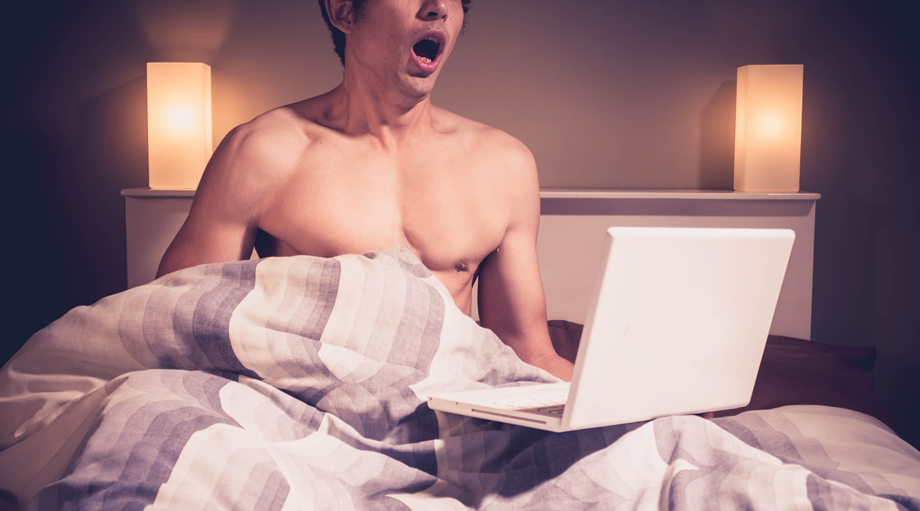 Shirtless man in bed with laptop that could benefit from masturbation training