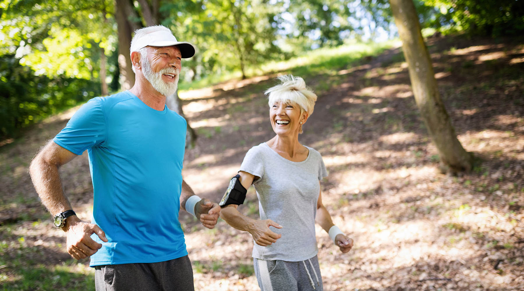 Happy older couple running in the woods after reversing erectile dysfunction