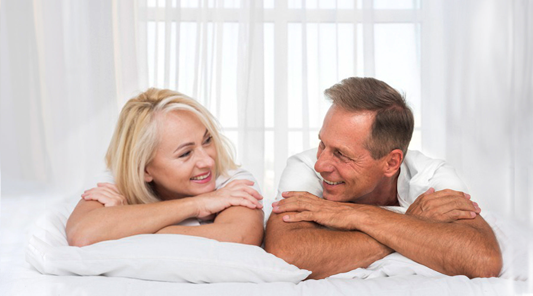 happy man and woman viewed from shoulders up in white bed with while background