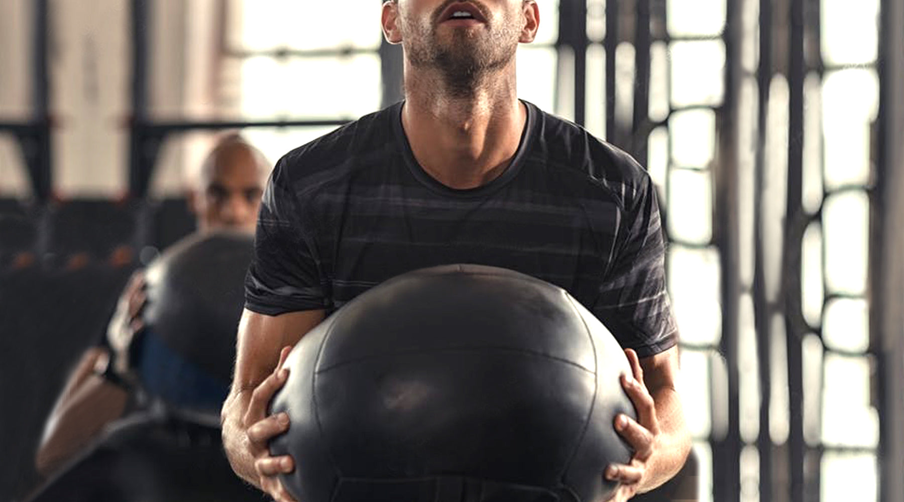 Man in black t-shirt holding medicine ball and exercising his pelvic muscles