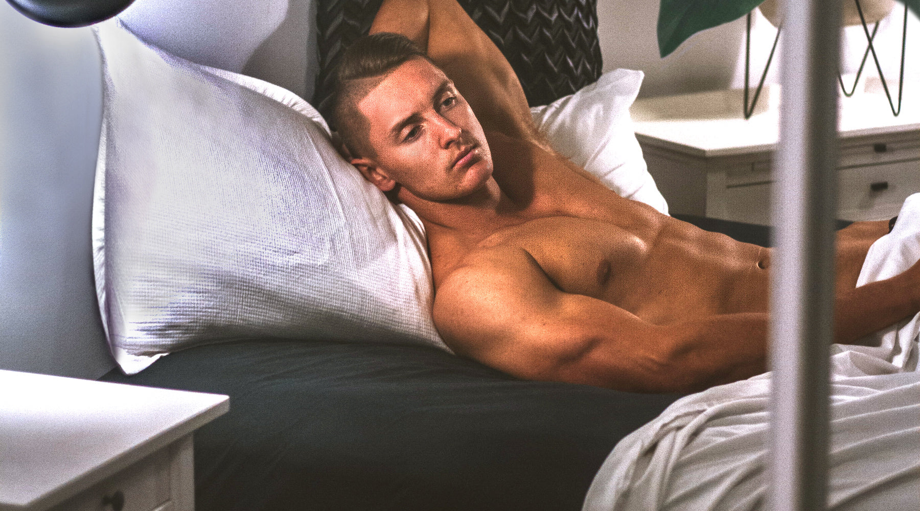fit man in bed appearing pensive about climaxing early