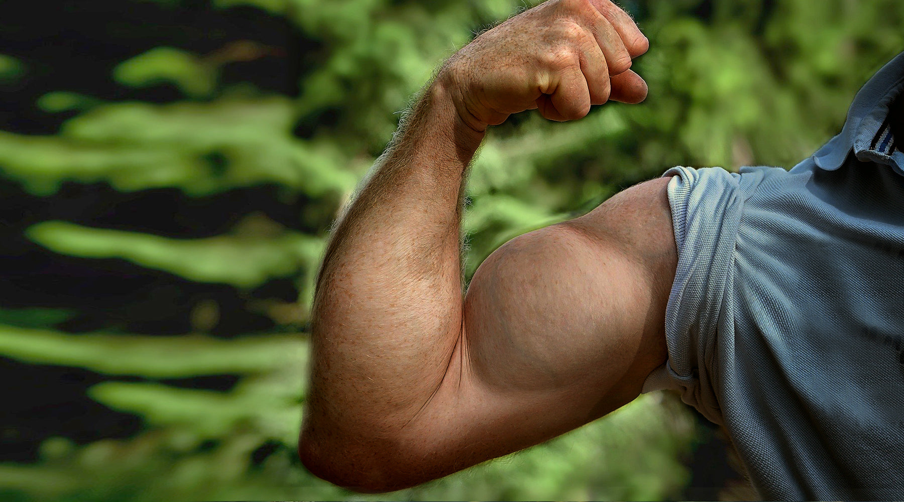 Man flexing bicep with a very strong arm, showing only shoulder and arm