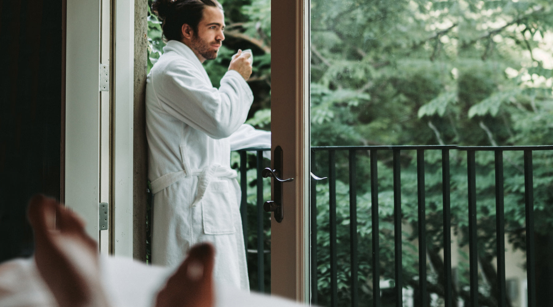 Man with hair pulled back in a white robe looking out the window and drinking coffee after a sexual encounter